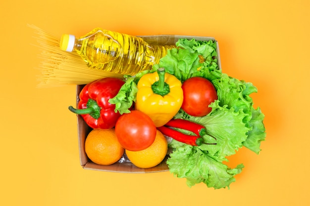 Cardboard box with food, sunflower oil, red, yellow pepper, chili, oranges, tomatoes, pasta, isolated over a yellow space