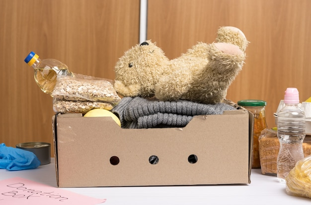 Cardboard box with food and things to help those in need, concept of help and volunteering