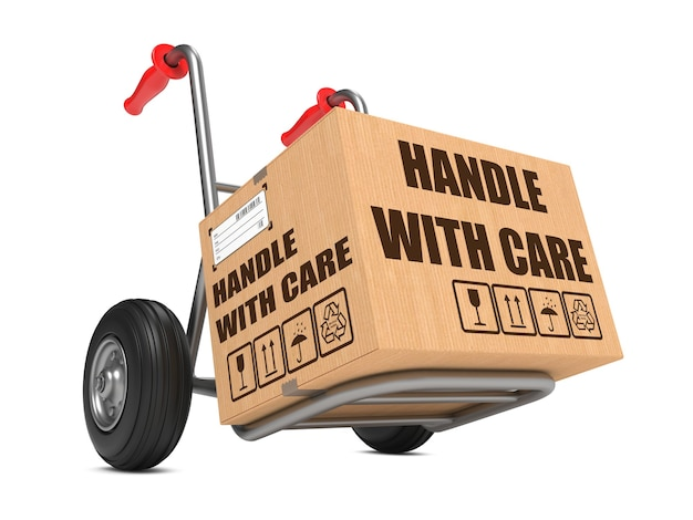 Cardboard box with handle with care slogan on hand truck isolated on white background.