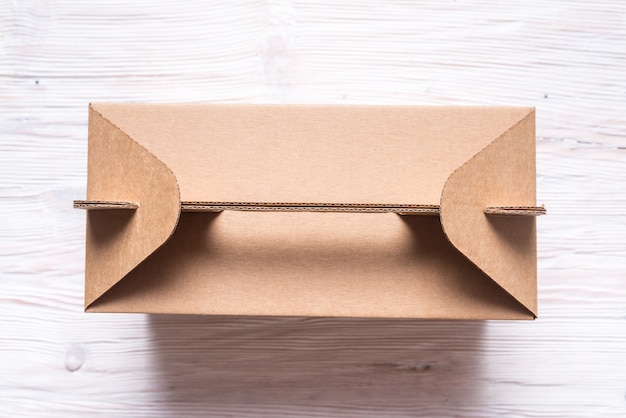 Cardboard box with handle on wooden table