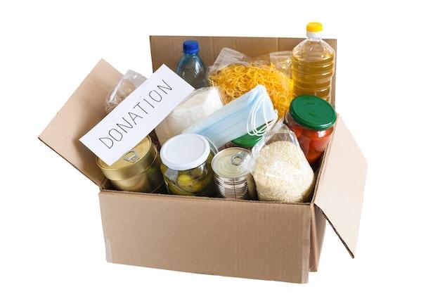 油、缶詰、シリアル、パスタが入った段ボール箱。さまざまな食べ物が入った募金箱。孤立