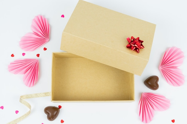 Cardboard box with paper hearts and chocolates concept of valentine's day