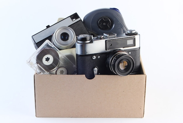 Cardboard box with retro film camera, audio cassette, gamepad on a white