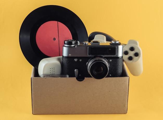 Cardboard box with retro film camera, gamepad, vinyl record, phone tube on yellow