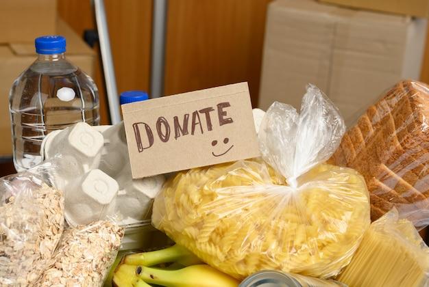 Картонная коробка с различными продуктами, фруктами, макаронами, подсолнечным маслом в пластиковой бутылке и консервации. концепция пожертвования