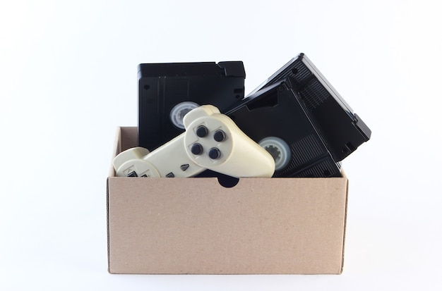 白のビデオカセットとゲームパッド付きの段ボール箱。骨董品、ゴミ箱