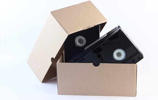 白のビデオカセットが付いている段ボール箱