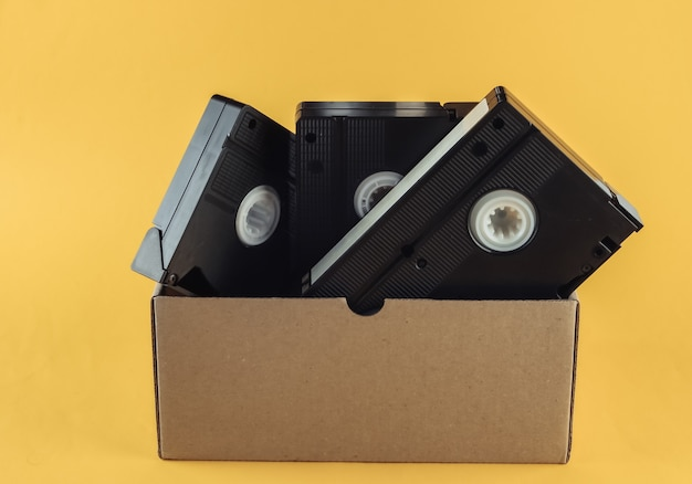 Cardboard box with video cassettes on a yellow
