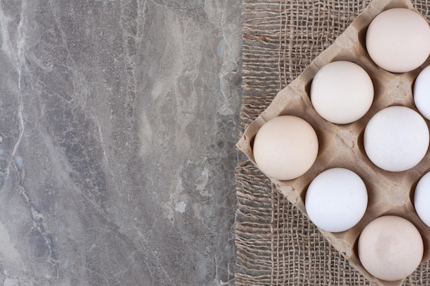 Картонная коробка с белыми куриными яйцами и пером. фото высокого качества
