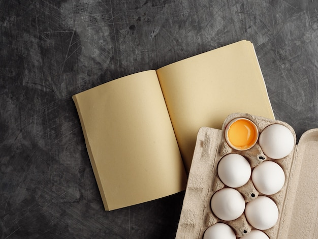 Cardboard box with white chicken eggs, craft paper recipe book on gray table. view from above.