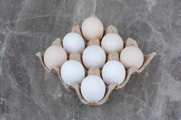 Cardboard box with white chicken eggs and feather. high quality photo