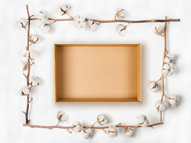 Cardboard box within frame made of cotton flower branches on white background. flat lay