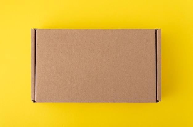 노란색 배경에 비문이나 그림이없는 골판지 상자. 공예 상자 평면도. 공간을 복사하십시오. 모의