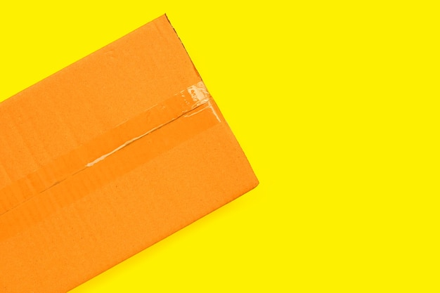Cardboard box on yellow background.