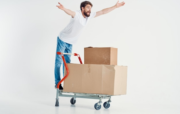 Cardboard boxes on a cargo trolley and happy men gesturing with hands copy space