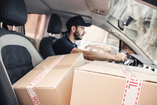 Cardboard boxes in front of delivery man driving vehicle