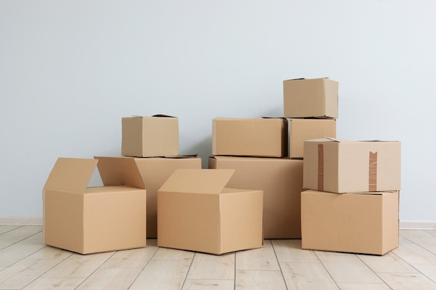 Cardboard boxes and household stuff in empty room