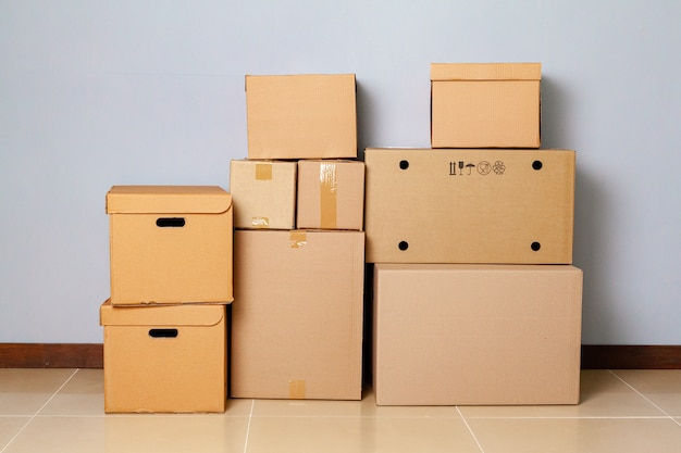 Cardboard boxes for moving on the floor against grey wall