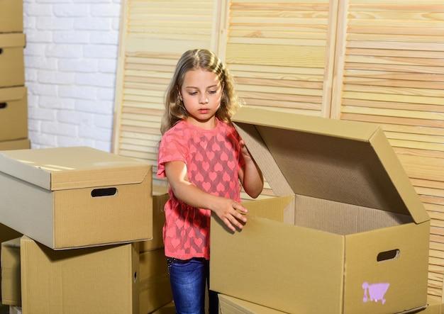 골판지 상자 - 새 집으로 이사. 행복한 아이 골판지 상자. 새 주거지 구입. 장난감으로 행복 한 어린 소녀입니다. 이동 개념입니다. 새 아파트. 훌륭한 편의 시설.