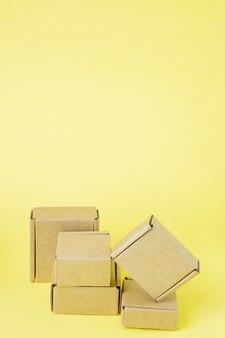 노란색 배경에 다양한 크기의 판지 상자.