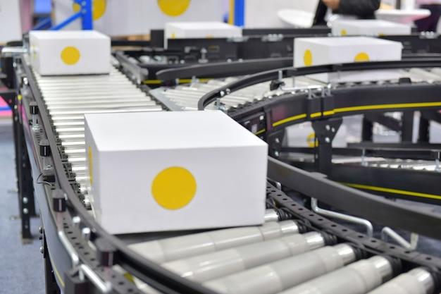 Картонные коробки на конвейерной ленте в концепции системы транспортировки посылок распределительного склада