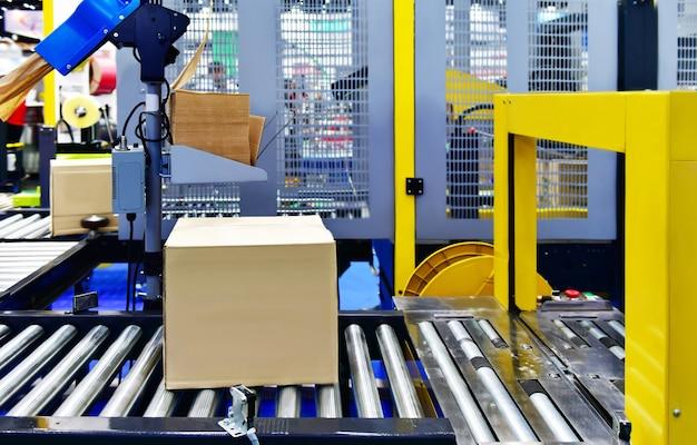 Картонные коробки на конвейерной ленте. концепция системы транспортировки посылок