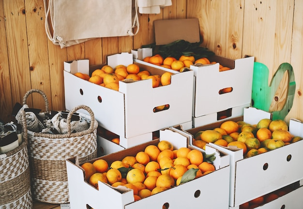 Cardboard boxes of organic tangerines in zero waste shop fresh fruits in plastic free store