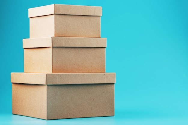 Cardboard boxes in the shape of a pyramid on a blue background.