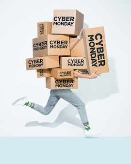 Cardboard boxes with cyber monday inscription in the hands of a young man