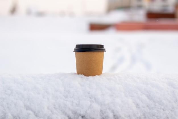 Картонная чашка кофе в снегу зимой. горячий пить чай или кофе в стакане зимой на улице.