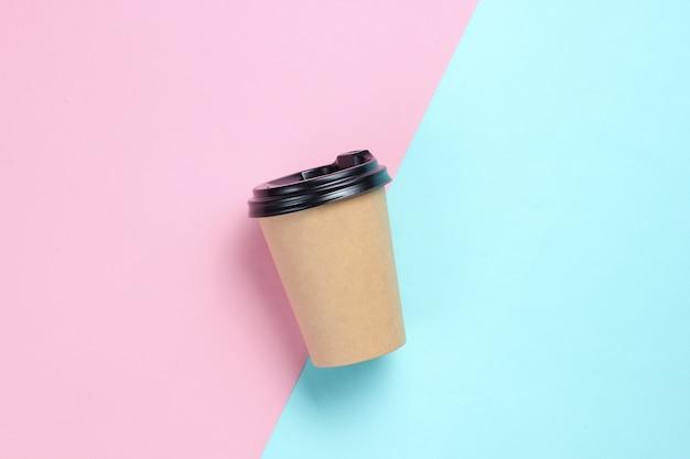 Картонная кофейная чашка на голубом розовом. вид сверху