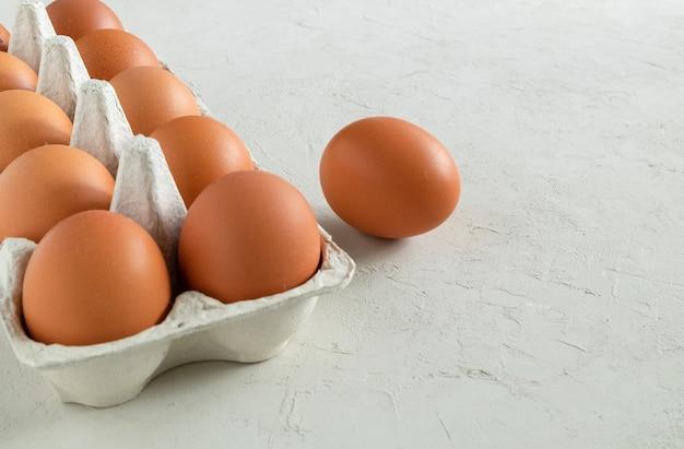 薄い灰色の漆喰の表面に新鮮な茶色の鶏の卵が入った段ボール容器