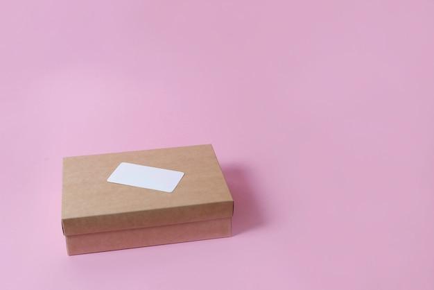ピンクの背景の上面図にカバー付きの段ボールクラフトボックス。配信の概念