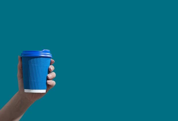 ミニマルな共同作業に行くためのコピースペースのホットドリンクと青い背景の上のコーヒーまたは紅茶の段ボールカップ...