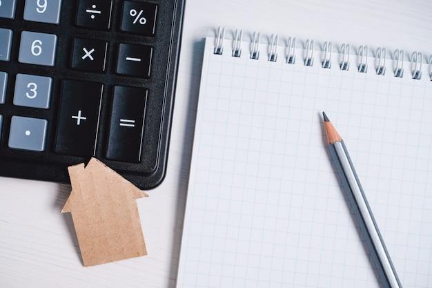 Картонный вырез дома, калькулятор и карандаш на чистый лист спиральной тетради