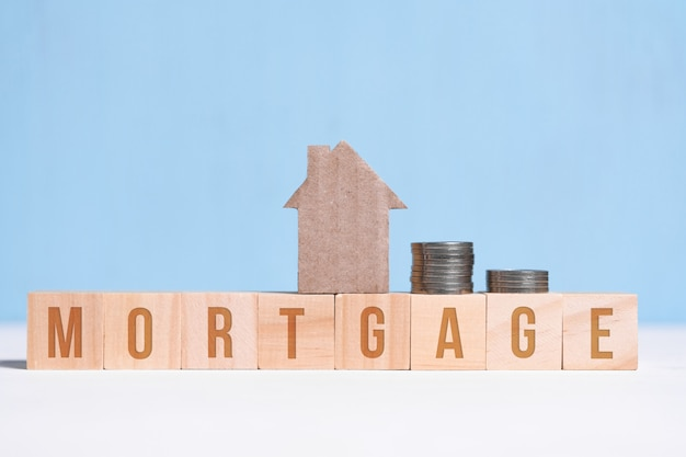 Cardboard cutout house and coins on cubes with inscription mortgage on blue .