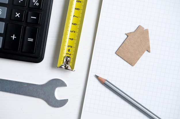 Cardboard cutout house, roulette, pencil, calculator, wrench and blank sheet of notebook.