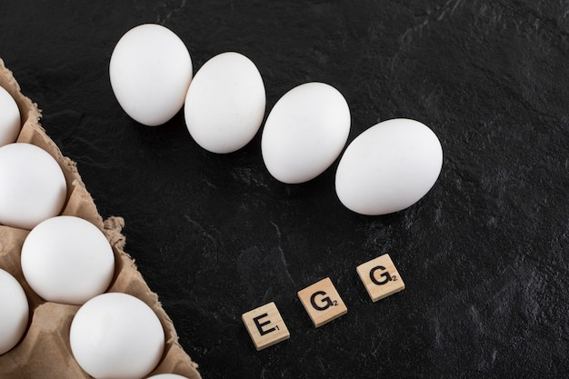 Cardboard egg box with white chicken eggs on a black table.
