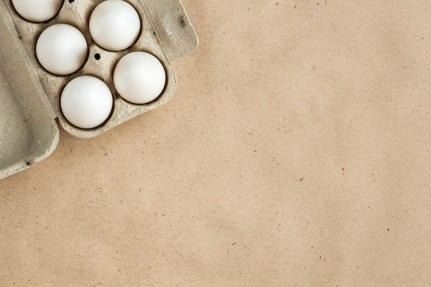 Cardboard egg rack with eggs on rustic background with copy space