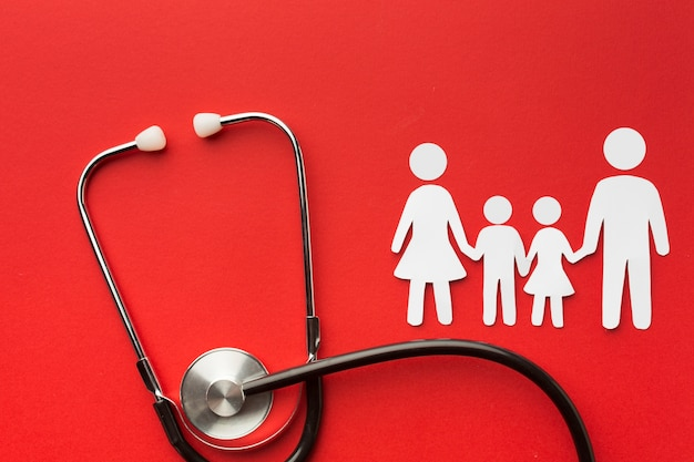 Семейство картонных фигур со стетоскопом на красном фоне