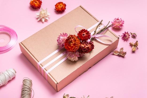 ピンクのテーブルにドライフラワーで飾られた段ボールのギフトボックス