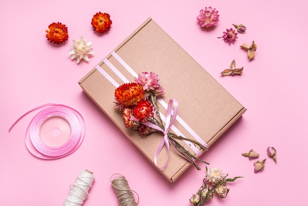 Cardboard gift box decorated with dried flowers on pink table