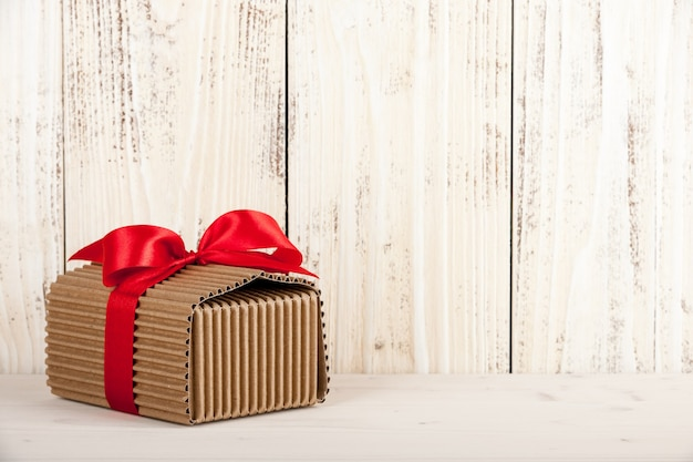 Cardboard gift box with red ribbon bow on wooden background