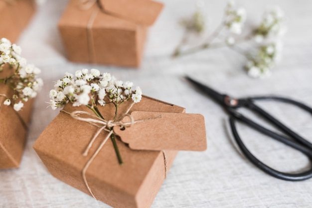 Cardboard gift boxes with tag and baby's-breath flowers on wooden desk