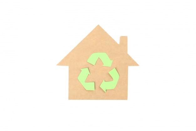 白い背景で隔離のリサイクルサインと段ボールの家