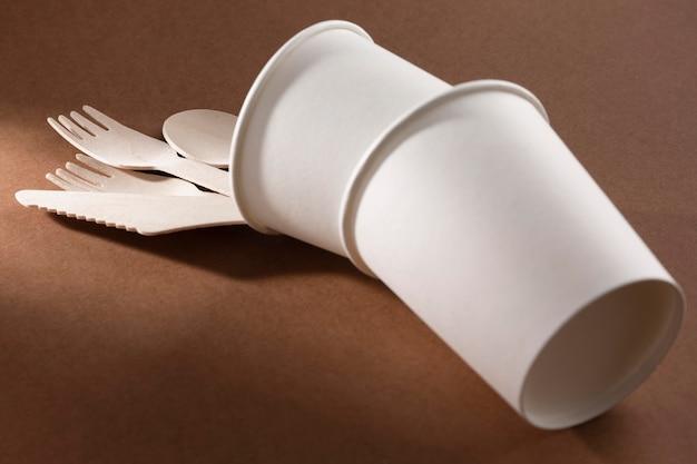 ひっくり返ったカップの段ボールのナイフとフォーク