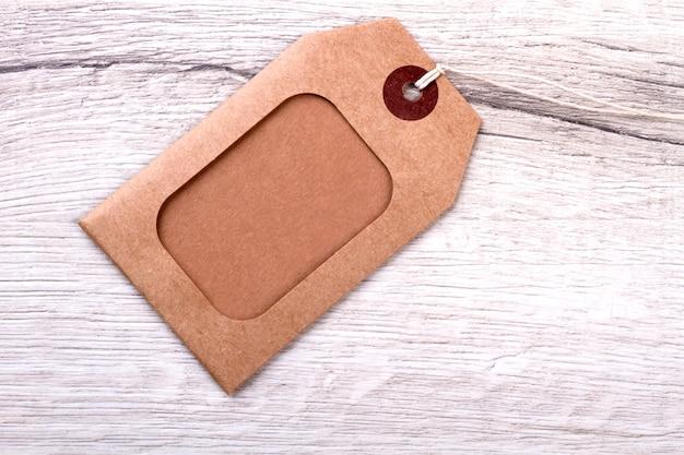木製の背景に段ボールのラベル。茶色のタグとサックスレッド。あなた自身のブランドを始めてください。価格はタグによって異なります。
