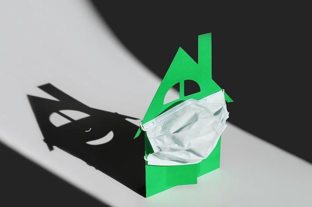 Картонный макет дома защищен входной дверью с медицинской маской.