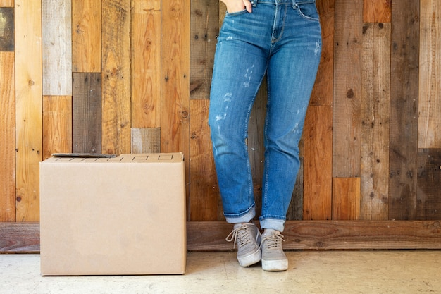 Cardboard moving boxes in empty room with wooden wall background and copy space, moving in new flat or house concept, retro design with legs sneakers and jeans.