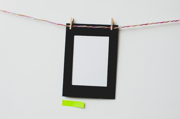 Cardboard photo frame and sticky note on white background